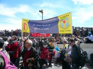 """Pielgrzymi z """"Talentu"""" z okazji beatyfikacji przygotowali transparent, na którym wiednieje prośba o wstawiennictwo bł. Jana Pawła II."""